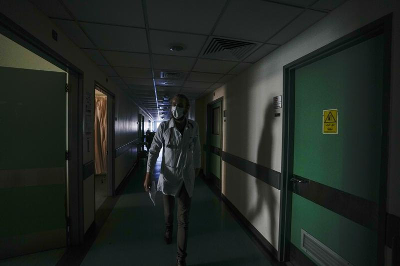 A doctor walks through a corridor of the government-run Rafik Hariri University Hospital during a power outage in Beirut, Lebanon, Wednesday, Aug. 11, 2021.  Many private hospitals, who offer 80% of Lebanon's medical services, are shutting down because of lack of resources or turning away patients who can't pay. (AP Photo/Hassan Ammar)