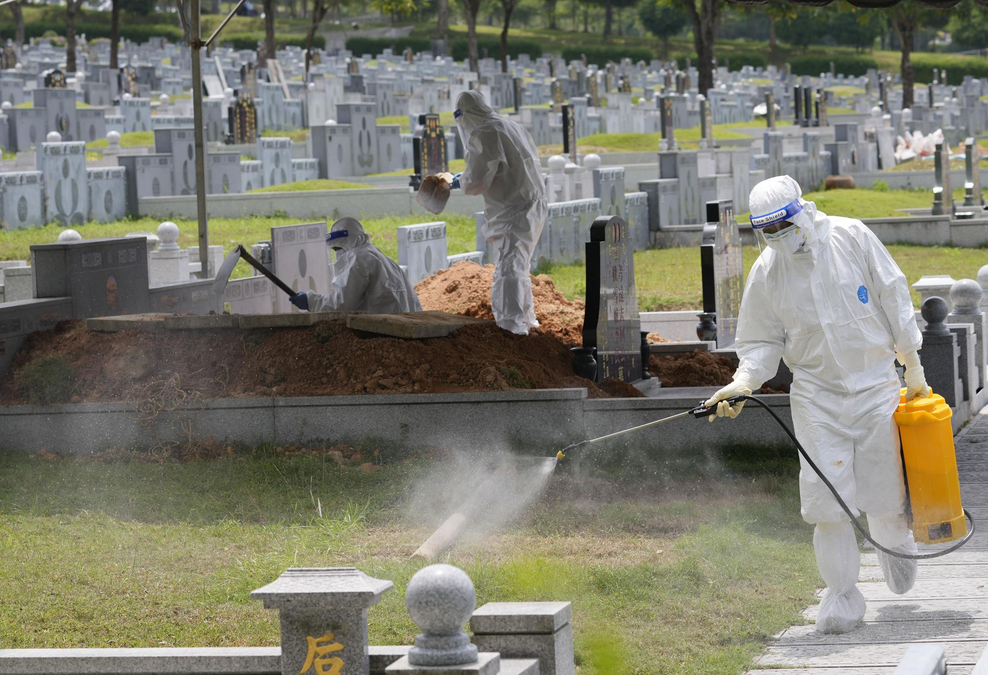 Health workers wearing Personal Protective Equipment (PPE) sanitize a field during the funeral for a COVID-19 victim at Nirvana memorial, a Buddhist, Taoist and Christian cemetery in Semenyih, Malaysia, Wednesday, May 26, 2021. Malaysia's latest coronavirus surge has been taking a turn for the worse as surging numbers and deaths have caused alarm among health officials, while cemeteries in the capital are dealing with an increasing number of deaths. (AP Photo/Vincent Thian)