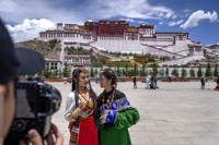 Chinese tourists in Tibetan dress pose for a photo at a square near the Potala Palace in Lhasa in western China's Tibet Autonomous Region, Tuesday, June 1, 2021. Tourism is booming in Tibet as more Chinese travel in-country because of the coronavirus pandemic, posing risks to the region's fragile environment and historic sites. (AP Photo/Mark Schiefelbein)