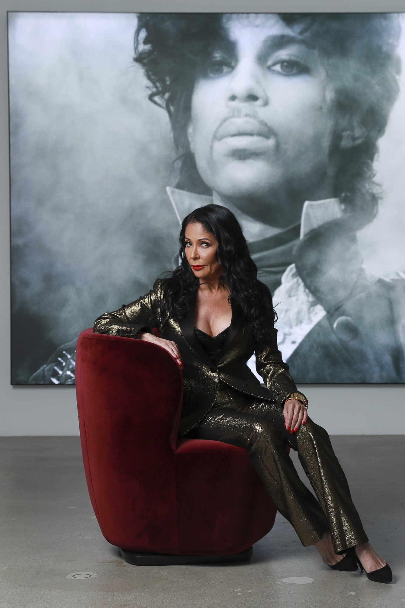 Apollonia Kotero poses for a portrait in front of a photo of Prince at Warner Music Group in Los Angeles on Friday, May 31, 2019. Kotero, who recorded Prince's