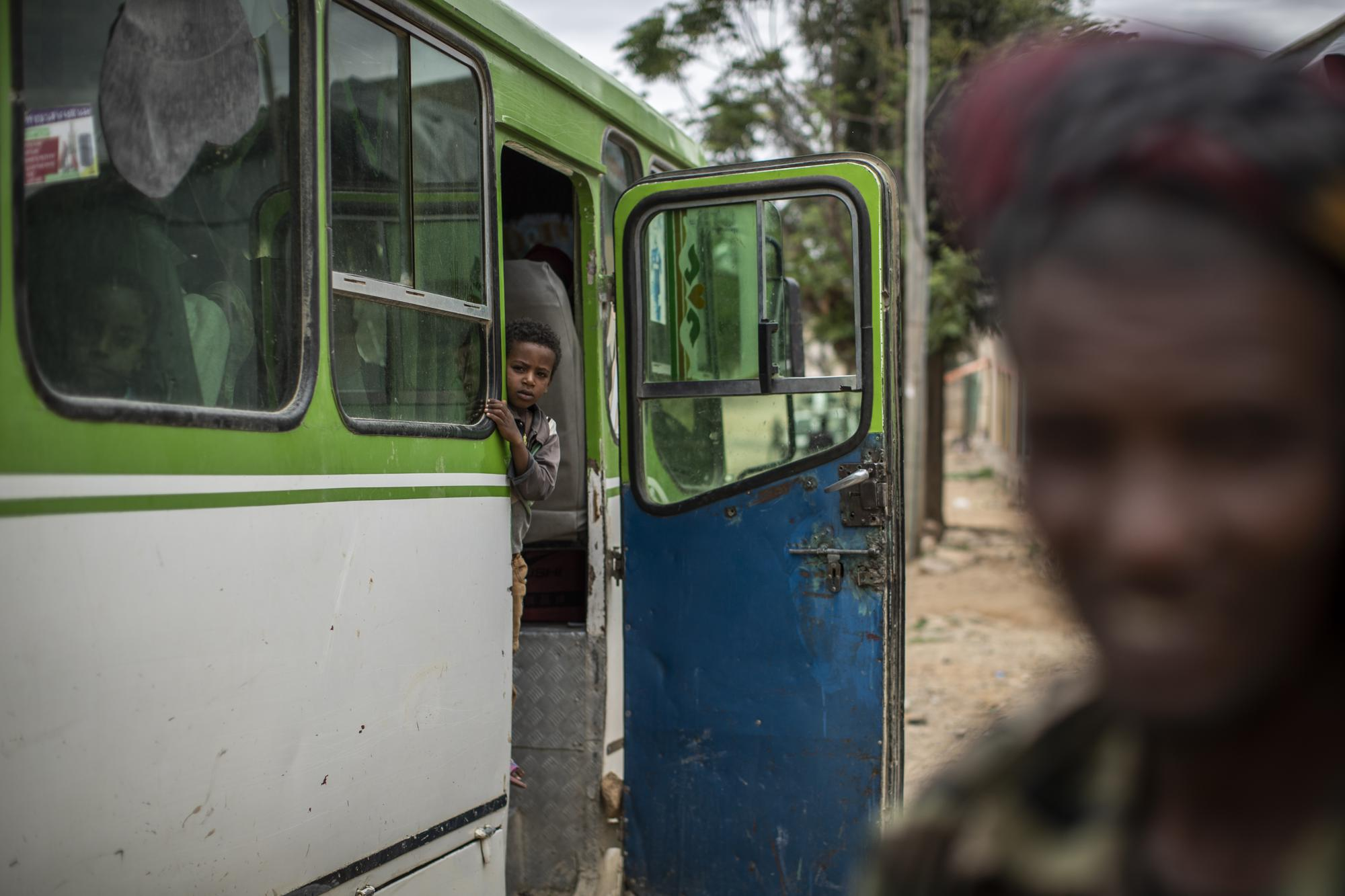 A boy about to depart on a bus looks towards a fighter loyal to the Tigray People's Liberation Front (TPLF), right, in the town of Hawzen, then-controlled by the group, in the Tigray region of northern Ethiopia, on Friday, May 7, 2021. Residents of Hawzen, a town of a few thousand people, said it had seen fighting four times since November. (AP Photo/Ben Curtis)