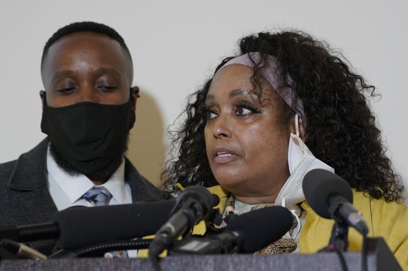 """Marcia Carter-Patterson, right, the mother of Manuel """"Manny"""" Ellis, stands with her son and Ellis' brother Matthew, left, as she speaks Thursday, May 27, 2021, at a news conference in Tacoma, Wash., south of Seattle. Ellis died on March 3, 2020 after he was restrained by police officers. Earlier in the day Thursday, Washington state attorney general filed criminal charges against three police officers in the death of Ellis. (AP Photo/Ted S. Warren)"""