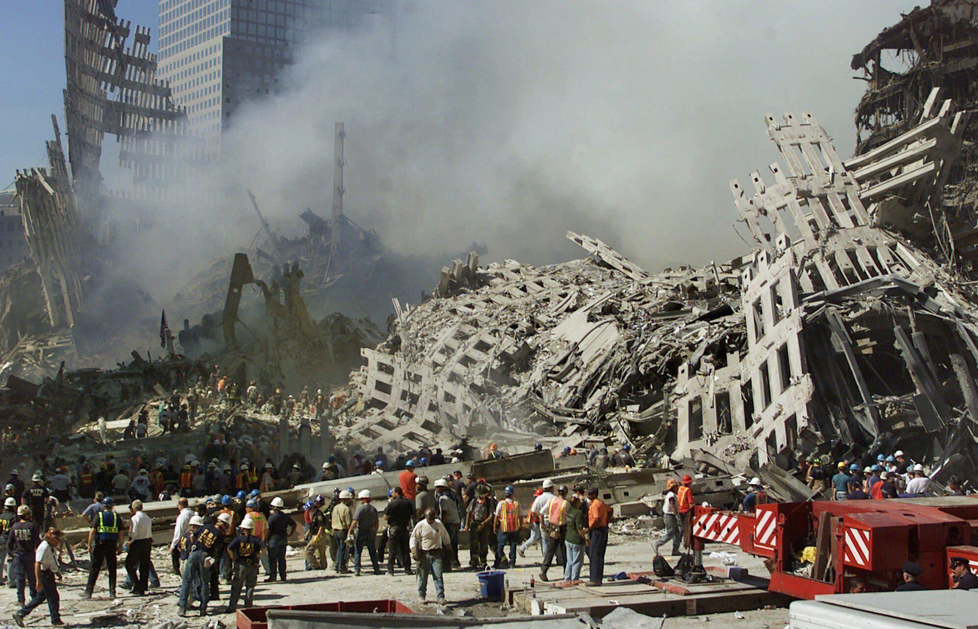 FILE - In this Thursday, Sept. 13, 2001 file photo, rescue workers continue their search as smoke rises from the rubble of the World Trade Center in New York. Twenty years on, the skepticism and suspicion first revealed by 9/11 conspiracy theories has metastasized, spread by the internet and nurtured by pundits and politicians like Donald Trump. One hoax after another has emerged, each more bizarre than the last: birtherism. Pizzagate. QAnon. (AP Photo/Beth A. Keiser, File)