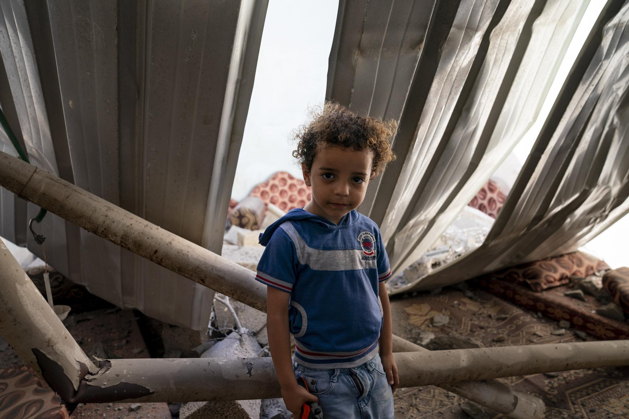 Mohammad Ismail, 4, sits for a portrait in his bedroom that was damaged when an airstrike destroyed a nearby building prior to a cease-fire that halted an 11-day war between Gaza's Hamas rulers and Israel, Thursday, May 27, 2021, in Maghazi, Gaza Strip. (AP Photo/John Minchillo)