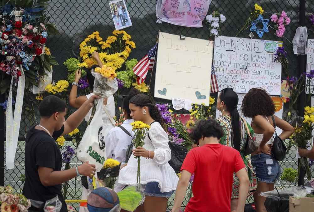 Los voluntarios junto con los lugareños reemplazan las flores muertas por otras frescas en un memorial improvisado para las víctimas del derrumbe del edificio de condominios Champlain Towers South, el martes 6 de julio de 2021, en Surfside, Florida (Carl Juste / Miami Herald vía AP)