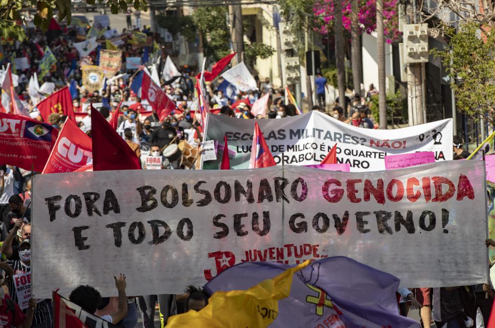 """Demonstranten marschieren mit einem Banner mit portugiesischer Botschaft;  """"Verschwinden Sie den Völkermord Bolsonaro und Ihre gesamte Regierung"""" während eines Protests gegen den brasilianischen Präsidenten Jair Bolsonaro und seinen Umgang mit der Pandemie und der Wirtschaftspolitik Demonstranten sagen, dass dies den Interessen der Armen und der Arbeiterklasse schadet, in Cuiaba, Brasilien, Samstag, 19. Juni 2021 June (AP Foto/Andre Penner)"""