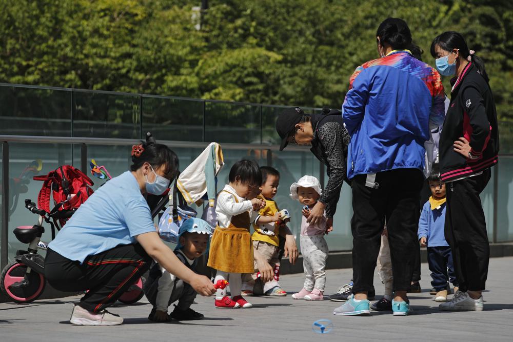 Moradores trazem seus filhos para brincar em um complexo próximo a um prédio comercial em Pequim em 10 de maio de 2021. O Partido Comunista da China vai reduzir os limites de natalidade para permitir que todos os casais tenham três filhos em vez de dois para lidar com o rápido aumento da média idade de sua população, disse uma agência de notícias estatal na segunda-feira, 31 de maio. (AP Photo / Andy Wong)