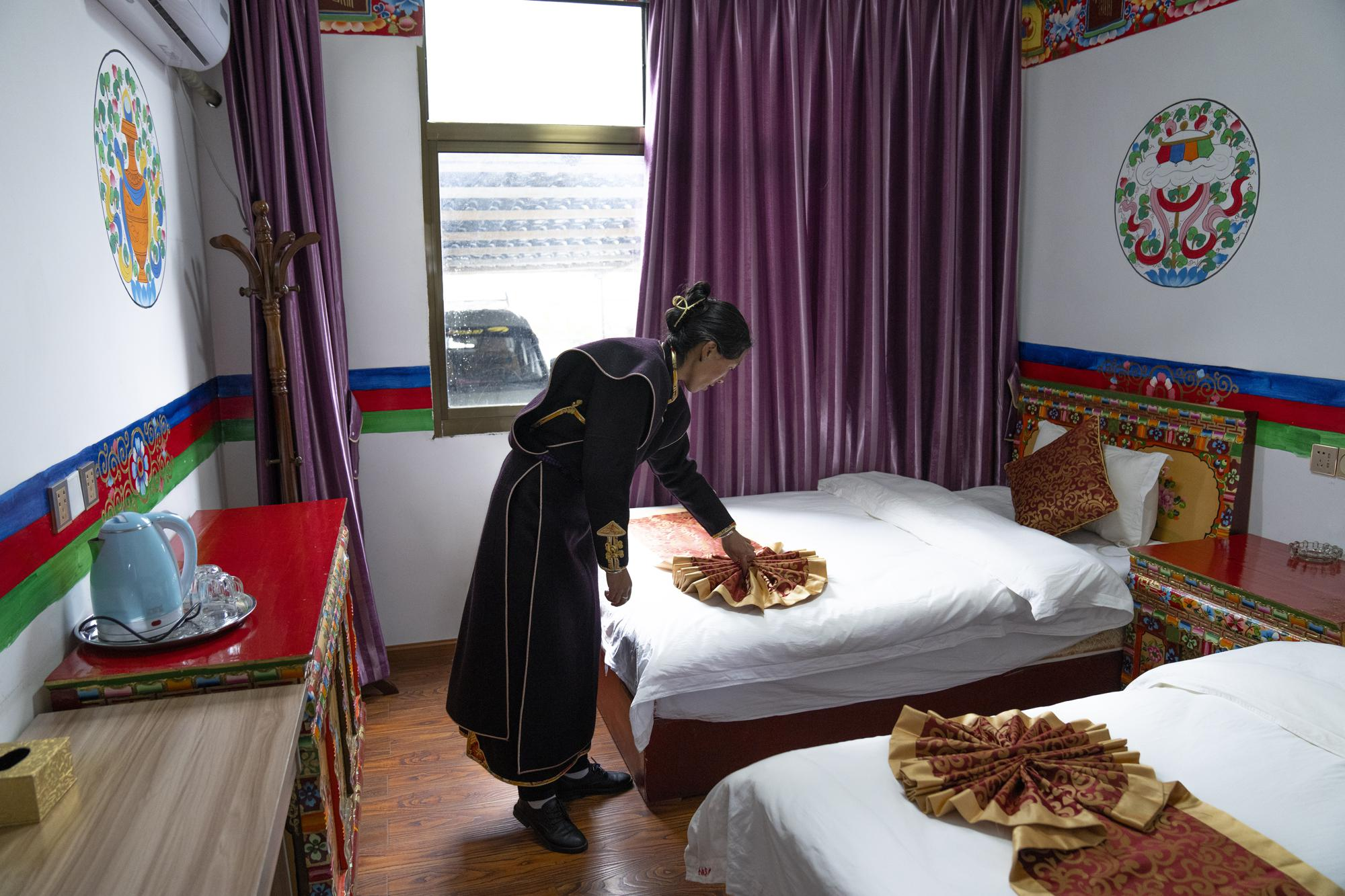 A woman in ethnic dress adjusts a bedspread at her tourist homestay in Zhaxigang village near Nyingchi in western China's Tibet Autonomous Region, Friday, June 4, 2021. Tourism is booming in Tibet as more Chinese travel in-country because of the coronavirus pandemic, posing risks to the region's fragile environment and historic sites. (AP Photo/Mark Schiefelbein)