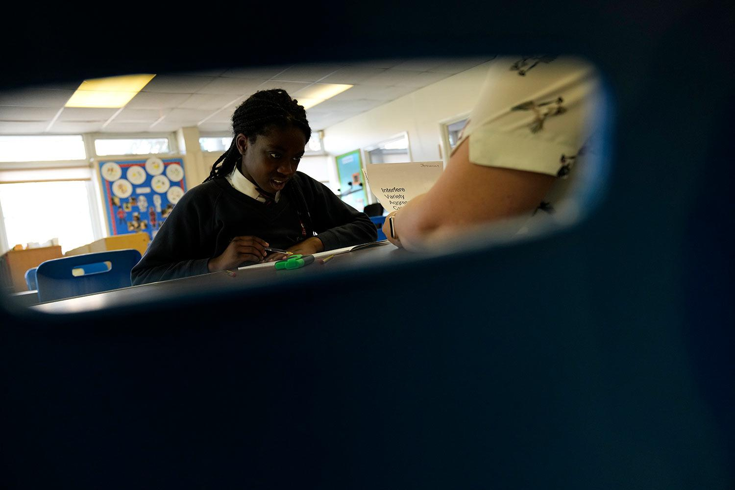 Ola listens to teacher Lorraine Eva as she has a spelling test at the Holy Family Catholic Primary School in Greenwich, London, Wednesday, May 19, 2021. (AP Photo/Alastair Grant)