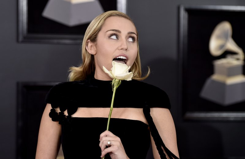 Miley Cyrus arrives at the Grammys with a rose
