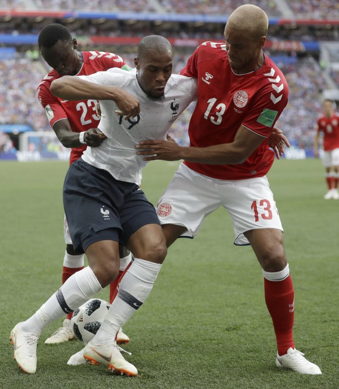 France's Djibril Sidibe, centre is tackled by Denmark's Pione Sisto, left, and Denmark's Mathias Jorgensen during the group C match between Denmark and France at the 2018 soccer World Cup at the Luzhniki Stadium in Moscow, Russia, Tuesday, June 26, 2018.