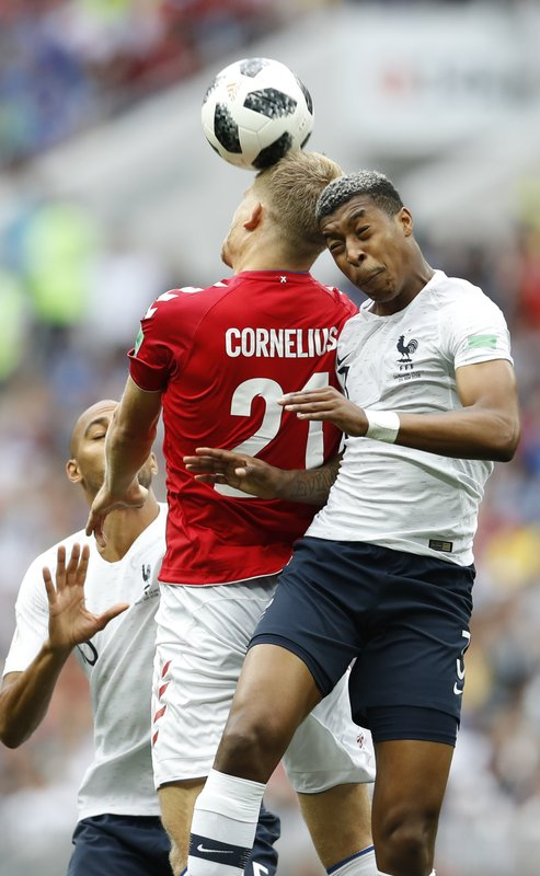 Denmark's Andreas Cornelius goes for a header with France's Presnel Kimpembe during the group C match between Denmark and France at the 2018 soccer World Cup at the Luzhniki Stadium in Moscow, Russia, Tuesday, June 26, 2018.
