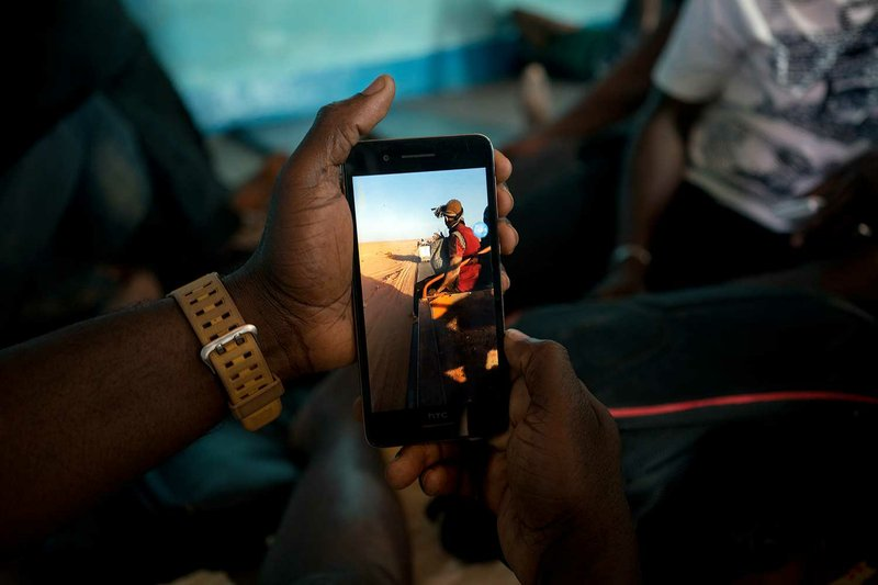 """Ju Dennis, from Liberia, holds his phone with which he filmed his plight through the Sahara after being expelled from Algeria, in an International Organization for Migration transit camp in the northern Nigerien desert city of Arlit on Friday, June 1, 2018. Dennis filmed his deportation with a cell phone he kept hidden on his body. """"You're facing deportation in Algeria _ there is no mercy,"""" he said. """"I want to expose them now... We are here, and we saw what they did. And we got proof."""" (AP Photo/Jerome Delay)"""