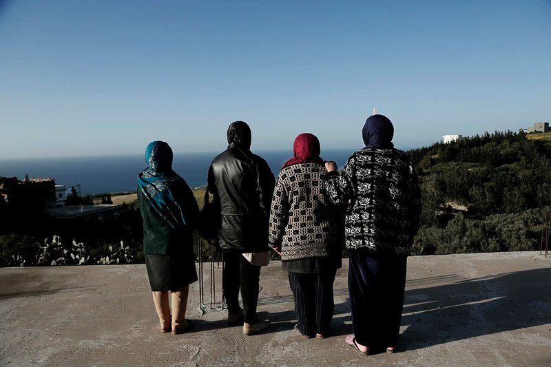 In this April 12, 2018 photo, women whose sons went missing look at the shoreline in the town of Ras Jabal, Bizerte, Tunisia. An Associated Press tally has documented at least 56,800 migrants dead or missing worldwide from 2014 to 2018 _ almost double the number found in the world's only official attempt to count them, by the U.N.'s International Organization for Migration. (AP Photo/Nariman El-Mofty)