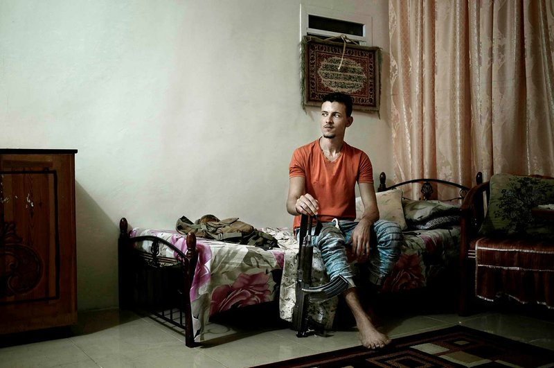 """In this Feb. 17, 2018 photo, 21 year-old Osama Ahmed, who fought during the '2015 battle of Aden' holds his rifle in his bedroom, at his home in Aden, Yemen. """"As a Yemeni citizen you can't leave the country - we are listed as terrorists - we had dreams and wanted to do things with our lives. There are no opportunity for the youth, we just want to live in peace without violence,"""" he said. (AP Photo/Nariman El-Mofty)"""