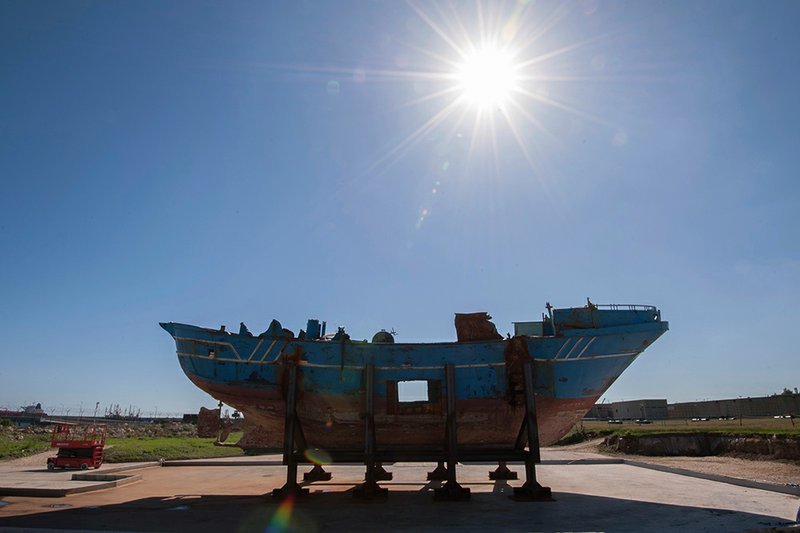 """FILE - In this Oct. 8, 2016 file photo, the hull of a fishing boat that capsized off the coast of Libya sits outside, at the NATO base in the Sicilian town of Melili, Italy. The story of the fishing boat known as the """"peschereccio"""" and its passengers reflects how migrants can simply vanish worldwide, sometimes without a trace. (AP Photo/Salvatore Cavalli, File)"""