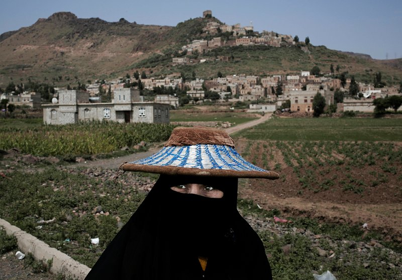 """In this Aug. 3, 2018 photo, a woman walks through Ibb, Yemen. Travelling across Yemen, an Associated Press team found """"in-between"""" moments everywhere _ Yemenis fitting their normal lives in between the destruction wreaked by four years of civil war. (AP Photo/Nariman El-Mofty)"""