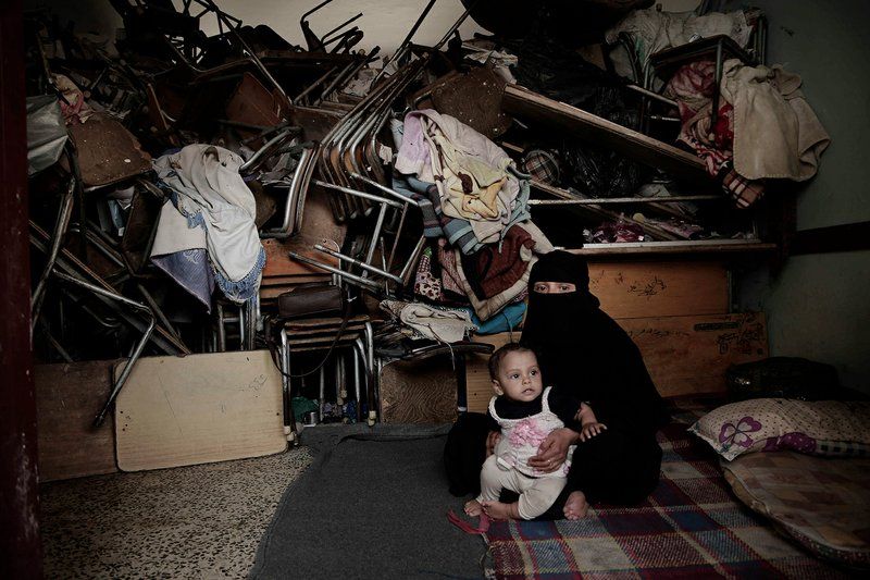 A woman sits with her baby inside a shelter for displaced persons in Ibb, Yemen, in this Aug. 3, 2018 photo. An AP investigation found that large amounts of international food aid is making into the country, but once there, the food often isn't getting to people who need it most. Factions on all sides of the conflict have kept food from communities not in their favor, diverted it to front-line combat units or sold it for profit on the black market, according to public records, confidential documents and interviews with aid workers, officials and average citizens. (AP Photo/Nariman El-Mofty)