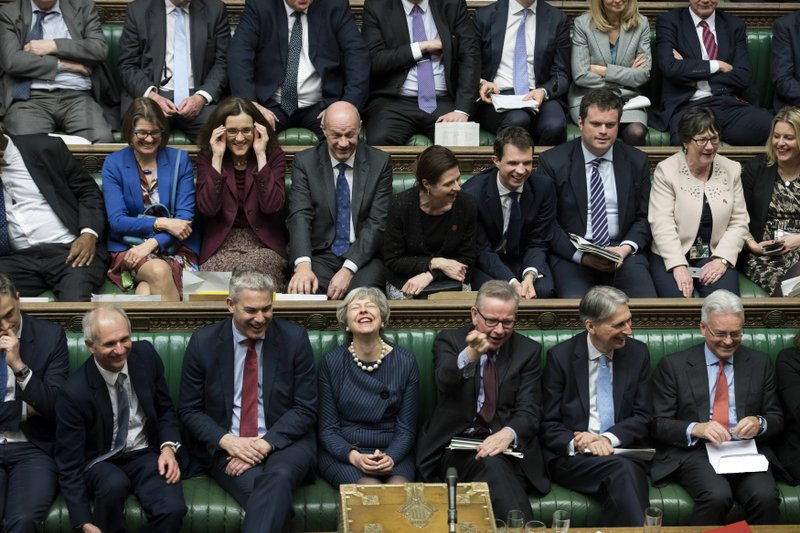 In this handout photo provided by UK Parliament, Britain's Prime Minister Theresa May, first row centre, laughs during the Brexit debate in the House of Commons, London, Thursday March 14, 2019. Britain's Parliament has voted to seek a delay of the country's departure from the European Union, a move that will likely avert a chaotic withdrawal on the scheduled exit date of March 29.  (UK Parliament/Jessica Taylor via AP)