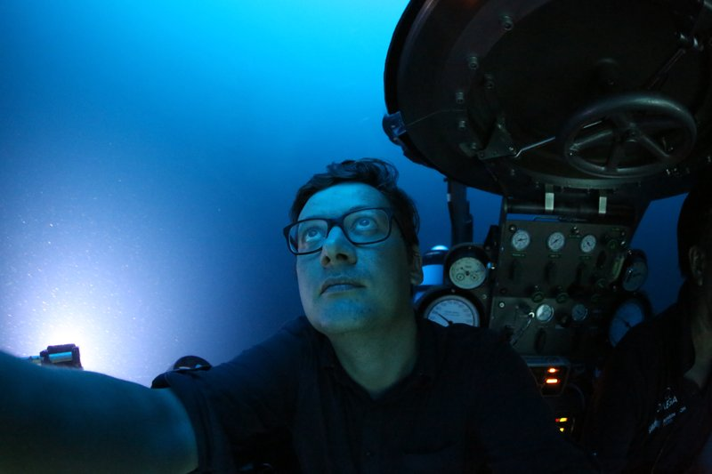 AP reporter, David Keyton, looks out of a submersible at around 400 feet below the surface off the coast of the island of St. Joseph in the Seychelles, April 8, 2019. (AP Photo/David Keyton)