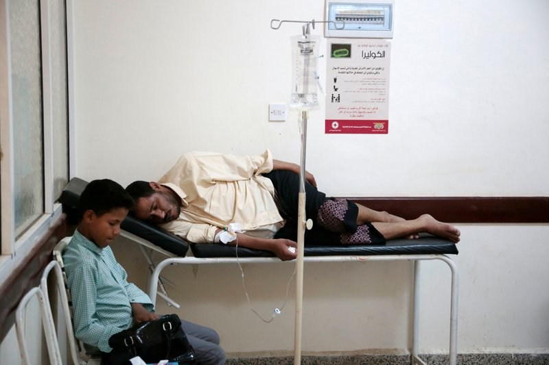 FILE - In this July 1, 2017 file photo, a man is treated for suspected cholera infection at a hospital in Sanaa, Yemen. An Associated Press investigation finds that Yemen's massive cholera epidemic was aggravated by corruption and official intransigence. The investigation has found that both the Iranian-backed Houthis rebels and their main adversary in the war -- the U.S.- and Saudi-backed government that controls southern Yemen -- impeded efforts by relief groups to stem the epidemic. (AP Photo/Hani Mohammed, File)