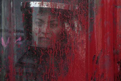 A police officer stands behind her riot shield covered in red paint during an International Women's Day march in Mexico City's main square, the Zocalo, Sunday, March 8, 2020. Protests against gender violence in Mexico have intensified in recent years amid an increase in killings of women and girls.(AP Photo/Rebecca Blackwell)
