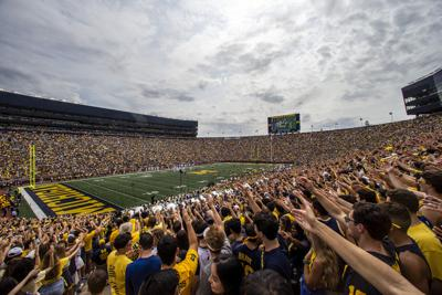 FILE - In this Saturday, Sept. 4, 2021, file photo, Michigan fans in the student section cheer during the second quarter of an NCAA college football game against Western Michigan at Michigan Stadium in Ann Arbor, Mich. As much as Big Ten teams love having fans back this year after playing without spectators in the pandemic-delayed 2020 season, the change is requiring some adjustments because communicating on the field isn't quite as easy as it was a year ago when they were in empty stadiums. (AP Photo/Tony Ding, File)