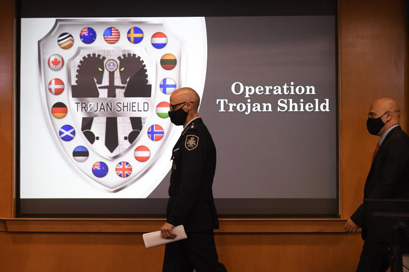 Law enforcement officials walk past an Operation Trojan Shield logo at a news conference, Tuesday, June 8, 2021, in San Diego. The global sting operation involved an encrypted communications platform developed by the FBI and has sparked a series of raids and arrests around the world in which more than 800 suspects were arrested and more than 32 tons of drugs — cocaine, cannabis, amphetamines and methamphetamines were seized. (AP Photo/Denis Poroy)