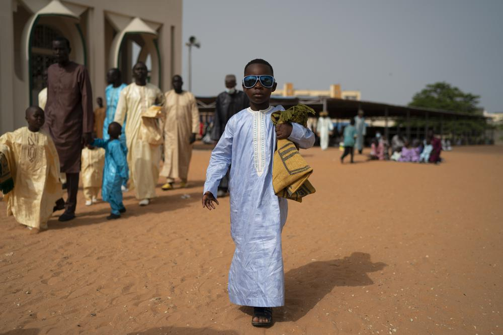 A boy leaves a mosque after attending the Eid al-Adha prayers in Dakar, Senegal, Wednesday, July 21, 2021. Health officials warn that COVID-19 cases are dramatically surging in the West African nation. (AP Photo/Leo Correa)