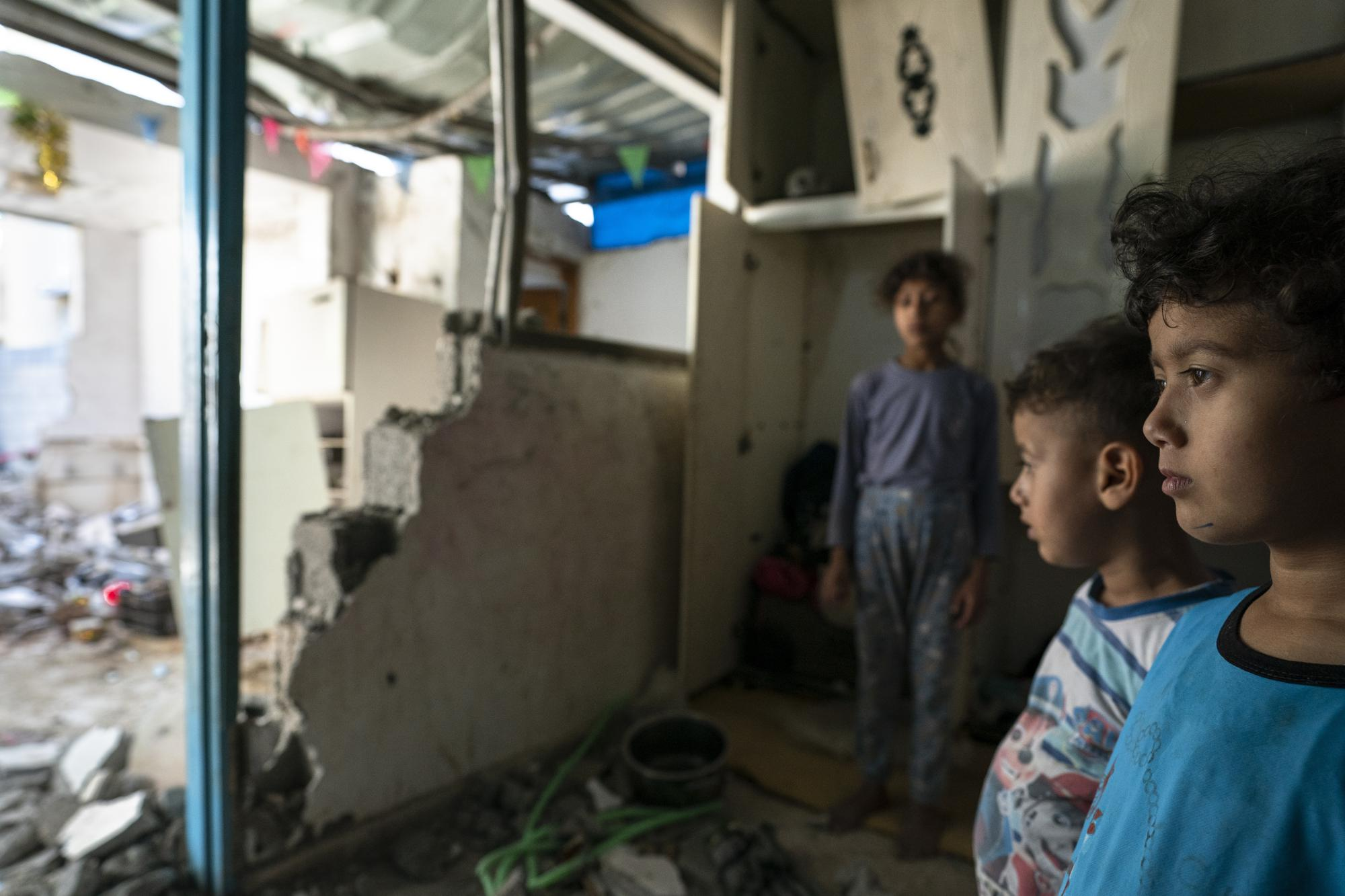 Batul Al-Masri, 5, and her siblings stand for a portrait in their bedroom that was damaged when an airstrike destroyed a nearby building prior to a cease-fire that halted an 11-day war between Gaza's Hamas rulers and Israel, Wednesday, May 26, 2021, in Beit Hanoun, Gaza Strip. (AP Photo/John Minchillo)