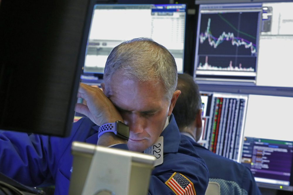 Stocks slip into a steep slide on Wall Street triggering automatic halt in trading