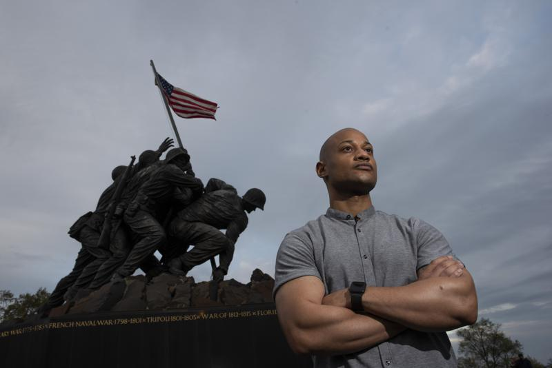 """Reserve Marine Maj. Tyrone Collier visits the U.S. Marine Corps War Memorial near his home in Arlington, Va., on Saturday, April 17, 2021. When Collier was a newly minted second lieutenant and judge advocate, he recalls a salute to him from a Black enlisted Marine. But even after Collier acknowledged the gesture, the salute continued. Puzzled, Collier asked why the Marine held it for so long. """"He said, 'Sir, I just have to come clean with something. ... We never see Black officers. We never see people like you and it makes me extraordinarily proud,'"""" Collier recalls. (AP Photo/Cliff Owen)"""