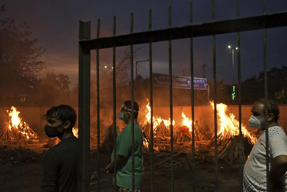 FILE - In this May 6, 2021, file photo, people watch burning funeral pyres of their relatives who died of COVID-19 in a ground that has been converted into a crematorium in New Delhi, India. India's excess deaths during the pandemic could be a staggering 10 times the official COVID-19 toll, likely making it modern India's worst human tragedy, according to the most comprehensive research yet on the ravages of the virus in the south Asian country. (AP Photo/Ishant Chauhan, File)