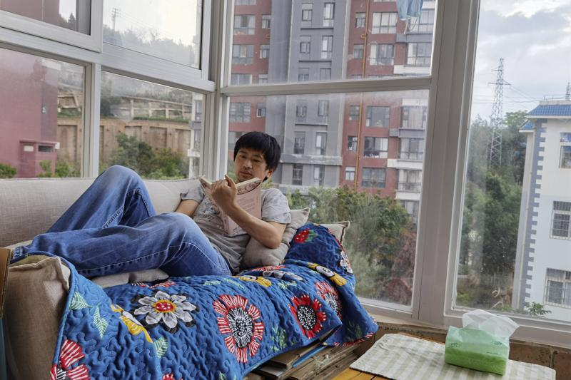 """In this photo released by Guo Jianlong, Guo reads a book at the balcony of his home in Dali in southwestern China's Yunnan province on June 29, 2021. Guo joined a small but visible handful of Chinese urban professionals who are rattling the ruling Communist Party by choosing to """"lie flat,"""" or reject grueling careers for what they call a """"low-desire life."""" That is clashing with the ruling party's message of success and consumerism as its celebrates the 100th anniversary of its 1921 founding. (Guo Jianlong via AP)"""