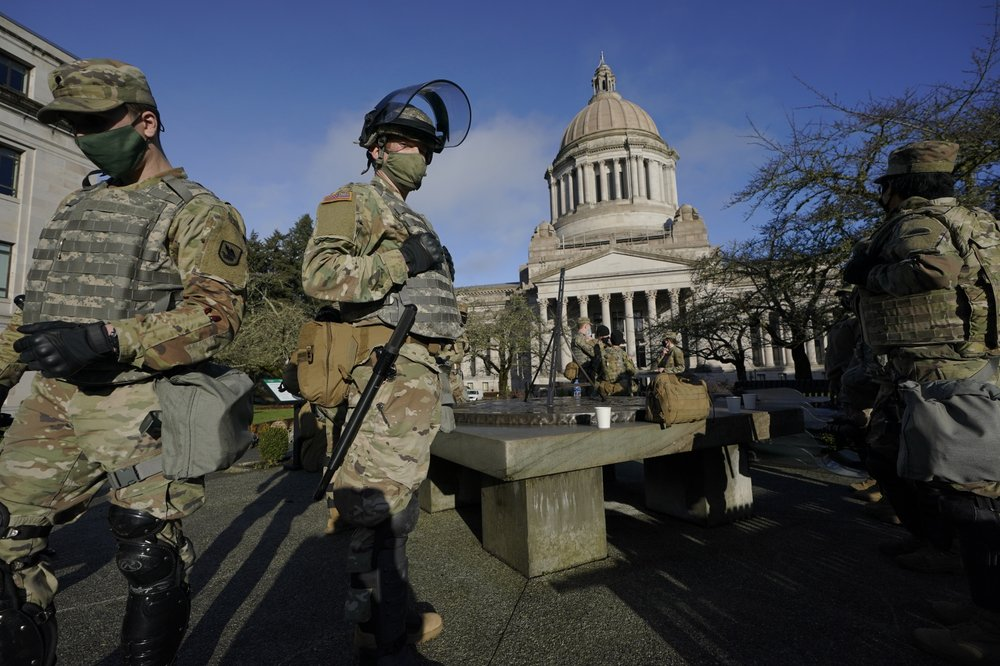 Small numbers of protesters gather at heavily fortified statehouses