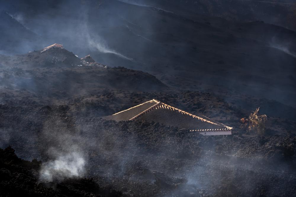 Una casa está cubierta de escombros después de la erupción de un volcán cerca de El Paso en la isla de La Palma en las Canarias, España, el martes 21 de septiembre de 2021. Un volcán inactivo en una pequeña isla española en el Océano Atlántico entró en erupción el domingo , obligando a la evacuación de miles de personas.  Enormes columnas de humo blanco y negro se dispararon desde una cresta volcánica donde los científicos habían estado monitoreando la acumulación de lava fundida debajo de la superficie.  (Foto AP / Emilio Morenatti)