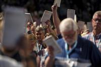 FILE - In this Wednesday, June 12, 2019 file photo, Bill Golden, and thousands of others, hold up copies of a training handbook related to sexual abuse within Southern Baptist churches during a speech by SBC President J. D. Greear on the second day of the SBC's annual meeting in Birmingham, Ala. As Southern Baptists prepare for their biggest annual meeting in more than a quarter-century in June 2021, accusations that leaders have shielded churches from claims of sexual abuse and simmering tensions around race threaten to once again mire the nation's largest Protestant denomination in a conflict that can look more political than theological. ( Jon Shapley/Houston Chronicle via AP, File)