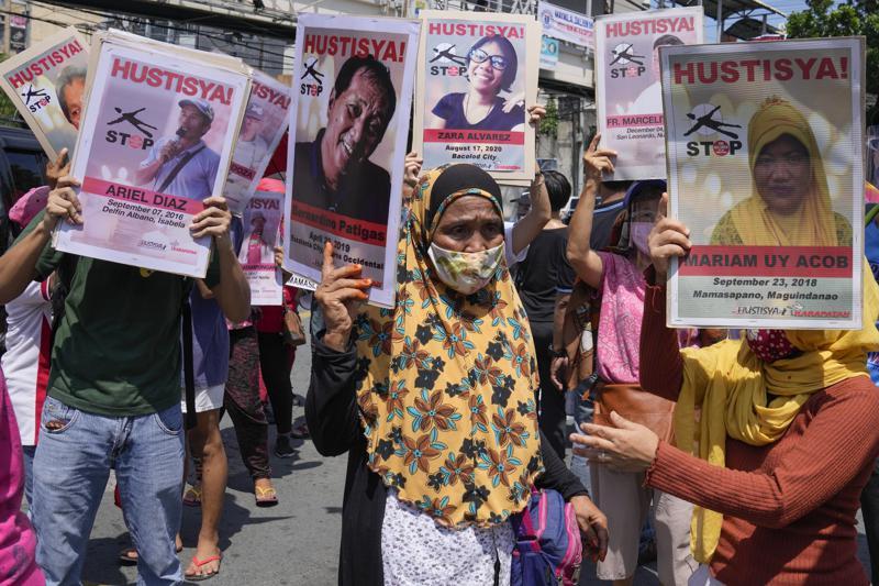Manifestantes portan retratos de presuntas víctimas de asesinatos extrajudiciales durante un acto frente al palacio Malacanang en Manila, Filipinas, miércoles 30 de julio de 2021. (AP Foto/Aaron Favila)