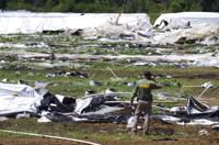 Josephine County Sheriff Dave Daniel stands amid the debris of plastic hoop houses destroyed by law enforcement, used to grow cannabis illegally, near Selma, Ore., on Wednesday, June 16, 2021. From dusty towns to forests in the West, illegal marijuana growers are taking water in uncontrolled amounts when often there isn't enough to go around for even licensed users.  . (Shaun Hall/Grants Pass Daily Courier via AP)