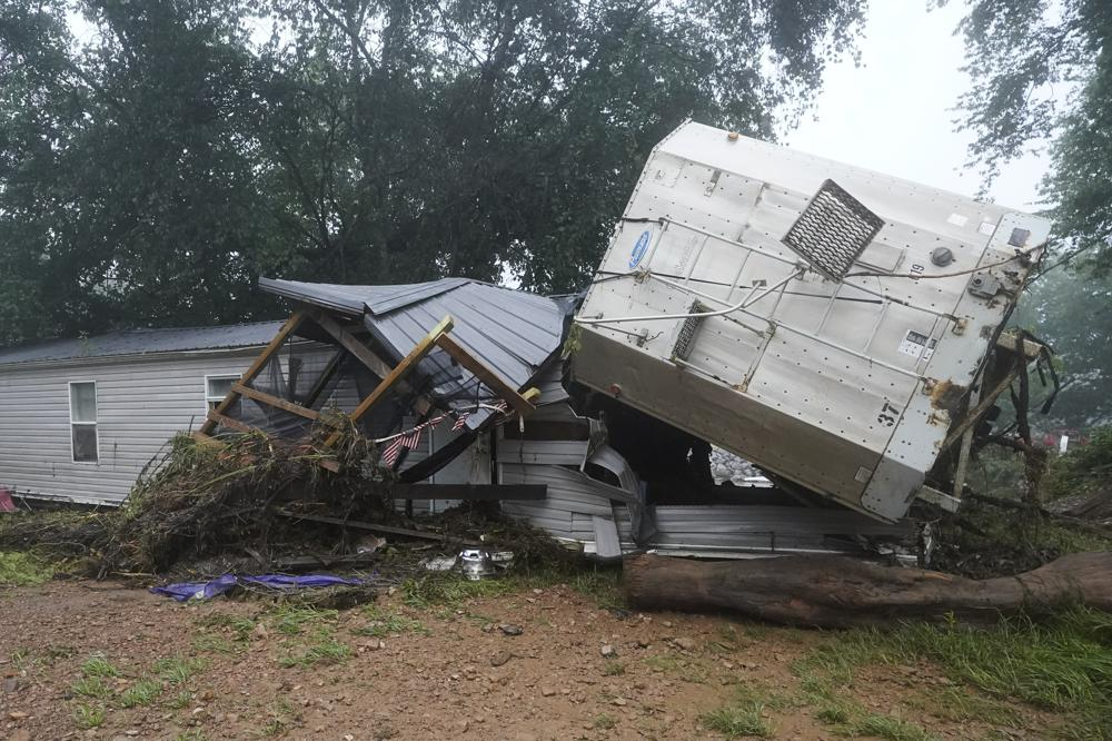 A mobile home and a truck trailer sit near a creek Sunday, Aug. 22, 2021, after they were washed away by flood waters the day before in McEwen, Tenn. Heavy rains caused flooding in Middle Tennessee and have resulted in multiple deaths as homes and rural roads were washed away. (AP Photo/Mark Humphrey)