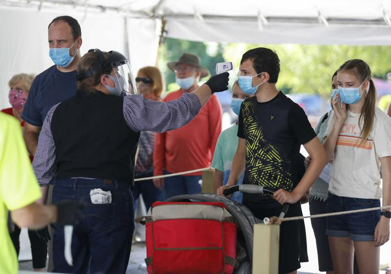 FILE - In this June 13, 2020, file photo, Silver Dollar City employee takes the temperature of guests before they are allowed to enter the park on just west of Branson, Mo. As the U.S. emerges from the COVID-19 crisis, Missouri is becoming a cautionary tale for the rest of the country: It is seeing an alarming rise in cases because of a combination of the fast-spreading delta variant and stubborn resistance among many people to getting vaccinated. (Nathan Papes/The Springfield News-Leader via AP, File)