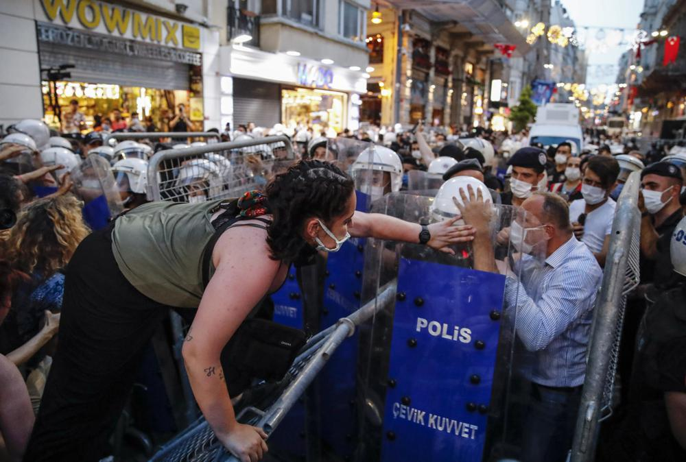 Protesters clash with police officers preventing them from marching against the government's decision to withdraw from Istanbul Convention, in Istanbul, Thursday, July 1, 2021. Turkey formally withdrew Thursday from the landmark international treaty protecting women from violence, and signed in its own city of Istanbul, though President Recep Tayyip Erdogan insisted it won't be a step backwards for women.  Women, LGBT groups and others have been protesting the decision, saying the convention's pillars of prevention, protection, criminal prosecution and policy coordination, as well as its identification of gender-based violence, are crucial to protecting women in Turkey.  (AP Photo/Kemal Aslan)