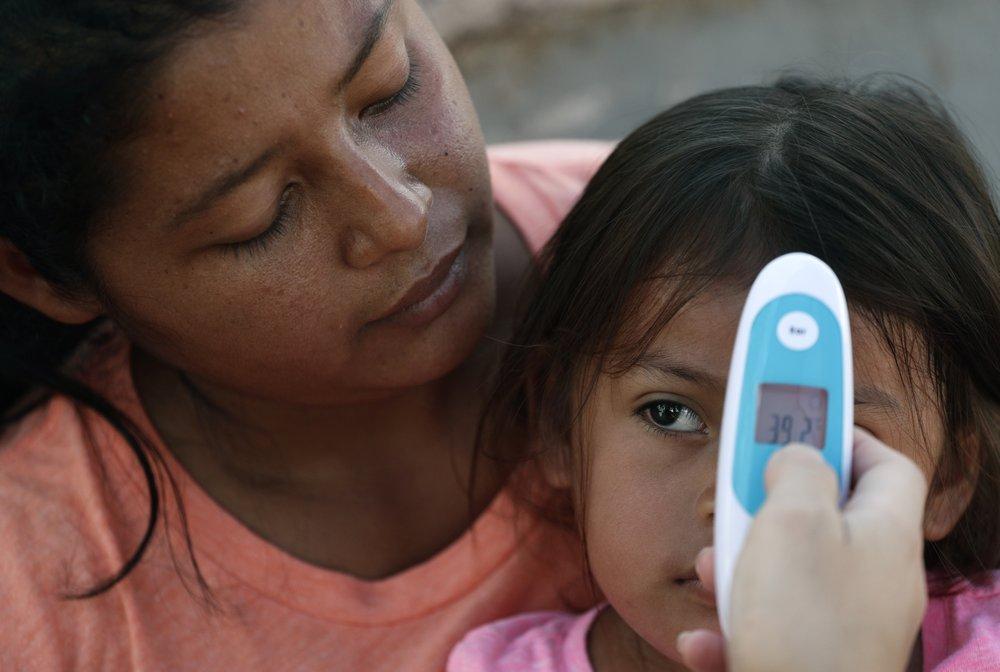 Nurse taking migrant child's temperature