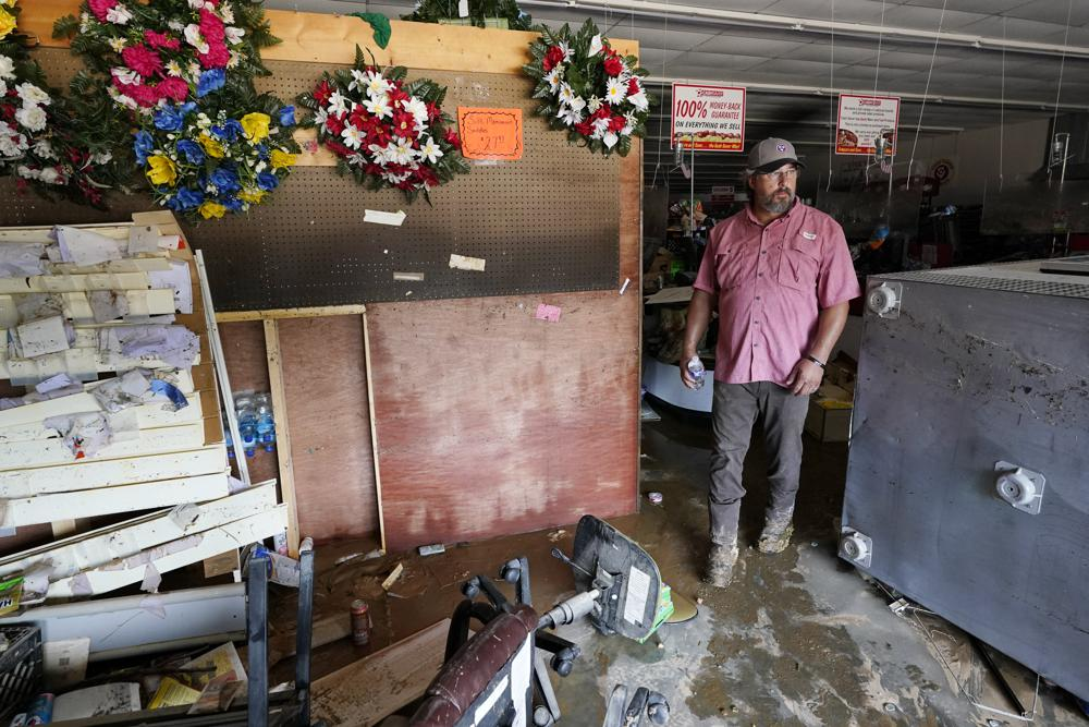 John Curtis, co-owner of Waverly Cash Saver grocery store, walks through his damaged store Sunday, Aug. 22, 2021, in Waverly, Tenn. Heavy rains caused flooding in Middle Tennessee and have resulted in multiple deaths as homes and rural roads were washed away. Curtis' store is the only grocery store in town. (AP Photo/Mark Humphrey)