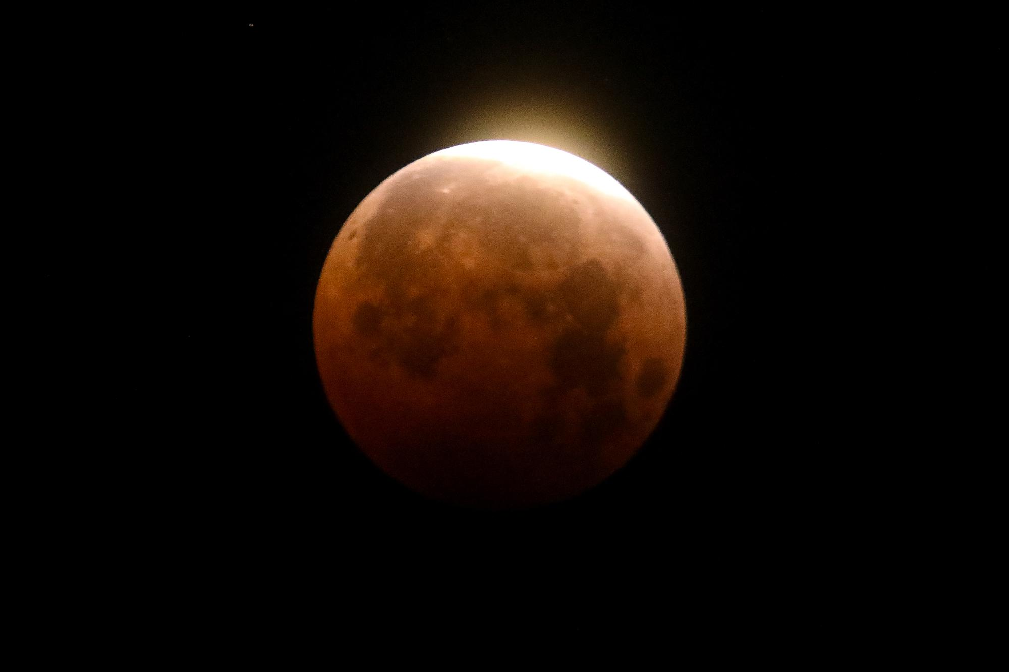 Light shines from a total lunar eclipse over Santa Monica Beach in Santa Monica, Calif., Wednesday, May 26, 2021. The first total lunar eclipse in more than two years is coinciding with a supermoon for quite a cosmic show. (AP Photo/Ringo H.W. Chiu)