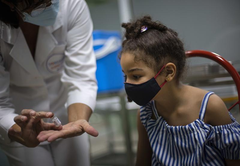 Una enfermera muestra un frasco de la vacuna Soberana-02 de fabricación cubana contra el COVID-19 antes de administrarle una dosis a una niña en La Habana, Cuba, el martes 24 de agosto de 2021. (AP Foto/Ramon Espinosa)