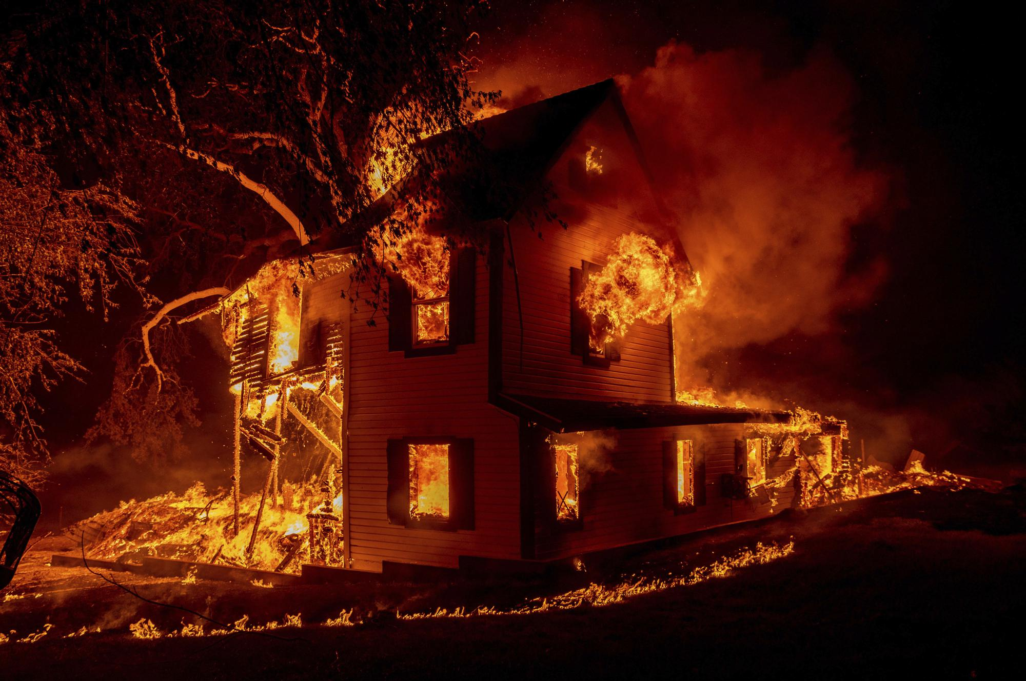 A home burns on Jeters Road as the Dixie fire jumps Highway 395 south of Janesville, Calif., on Monday, Aug. 16, 2021. (AP Photo/Ethan Swope)