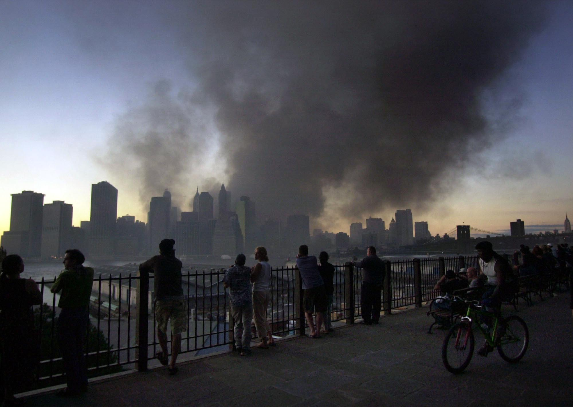 Pedestrians on Pierrepont Place in the Brooklyn borough of New York, watch as smoke billows from the remains of the World Trade Center in New York, Sept. 11, 2001. (AP Photo/Lawrence Jackson)