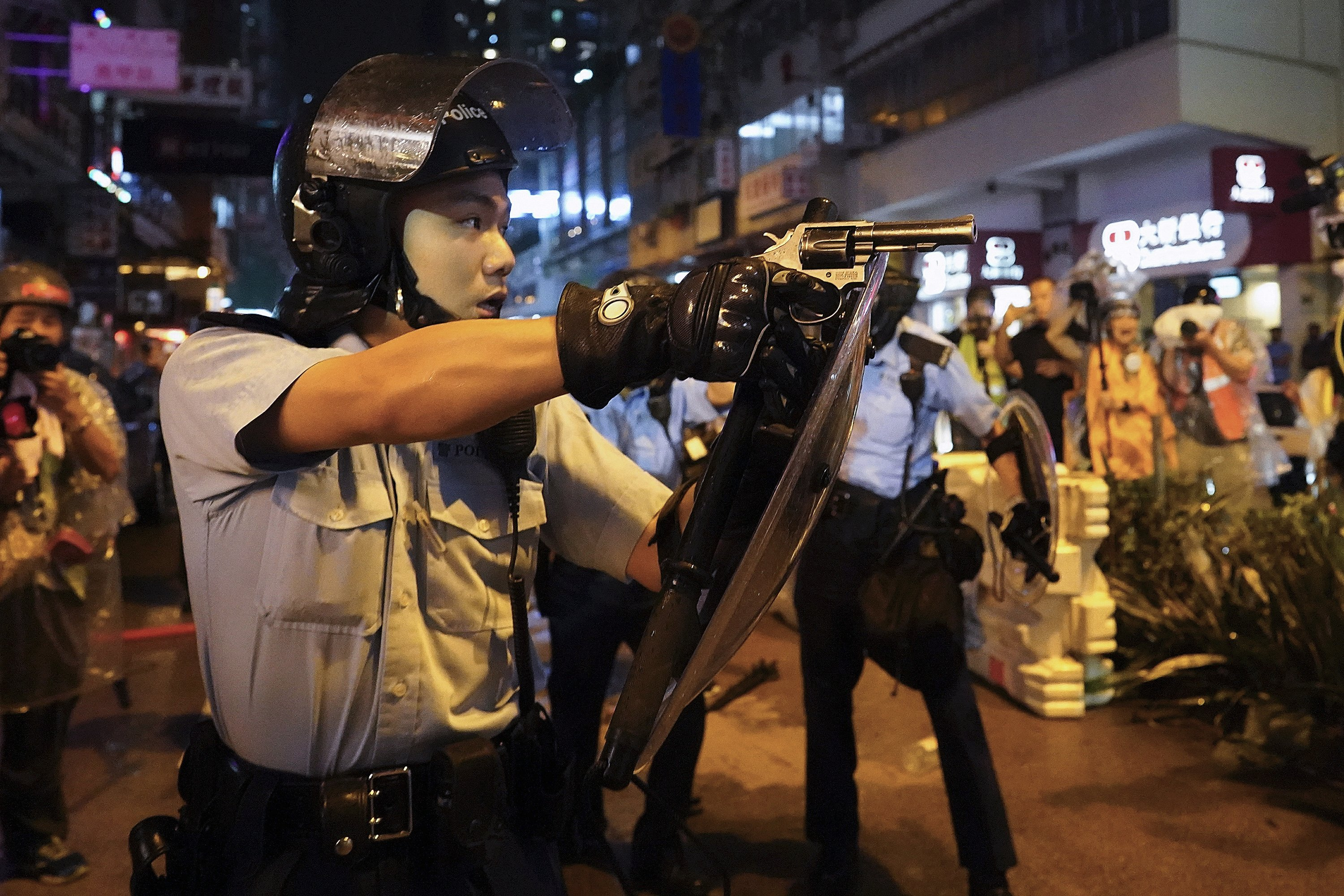 Hong Kong police draw guns, arrest 36 in latest protest