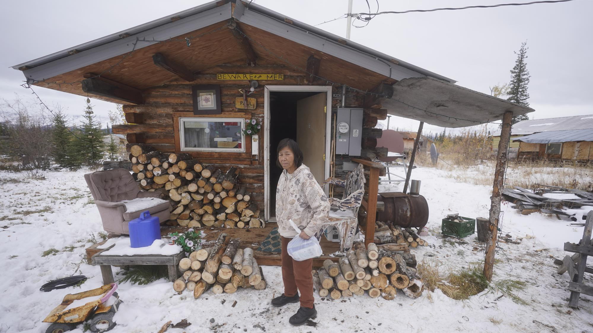 Marilyn Paul stands in front of her home Thursday, Sept. 23, 2021, in Tanacross, Alaska. Alaska is experiencing one of the sharpest rises in COVID-19 cases in the country, coupled with a limited statewide healthcare system that is almost entirely reliant on Anchorage hospitals. (AP Photo/Rick Bowmer)